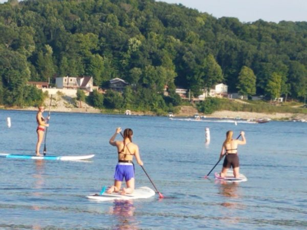 Several people paddle boarding on the lake.