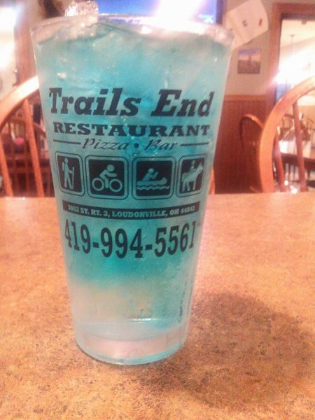 A blue colored ice beverage in a Trails End Restaurant glass.