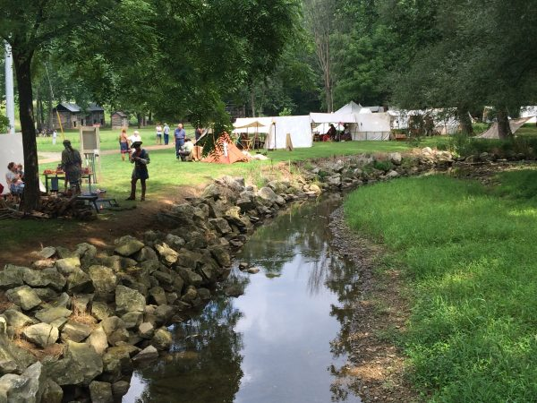 Tents, participants and visitors by the creek at the Grist Mill.