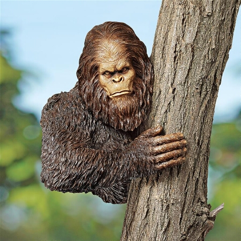 Big foot statue holding on to tree
