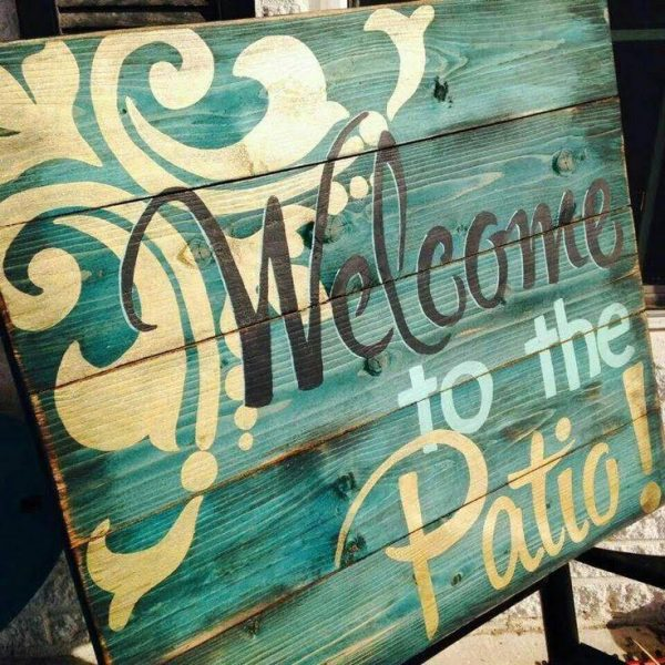 """Painted pallet wood sign that reads """"Welcome to the Patio""""."""