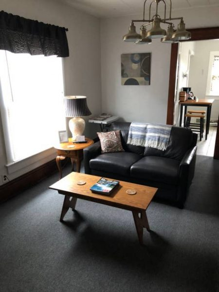Sofa and coffee table next to window in apartment.