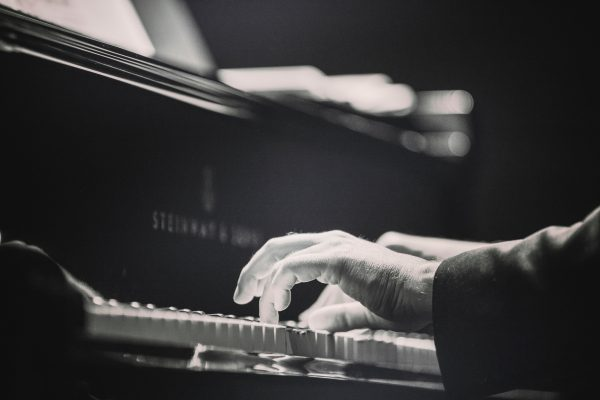 Black and white picture of hands on piano keys.