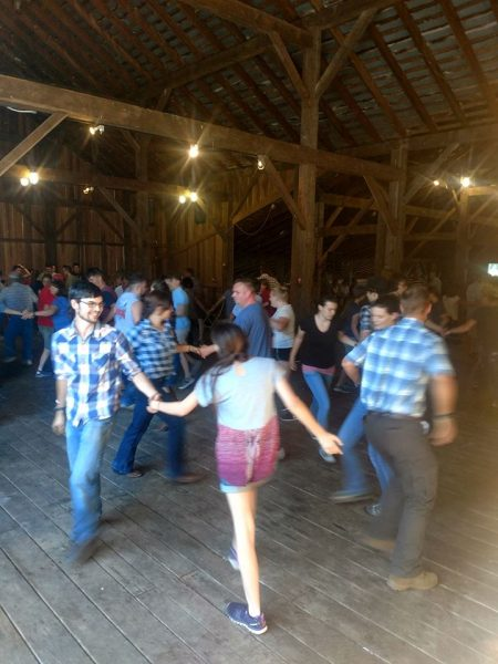 People square dancing in barn.
