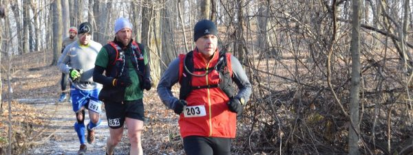 Man running trail race in woods.